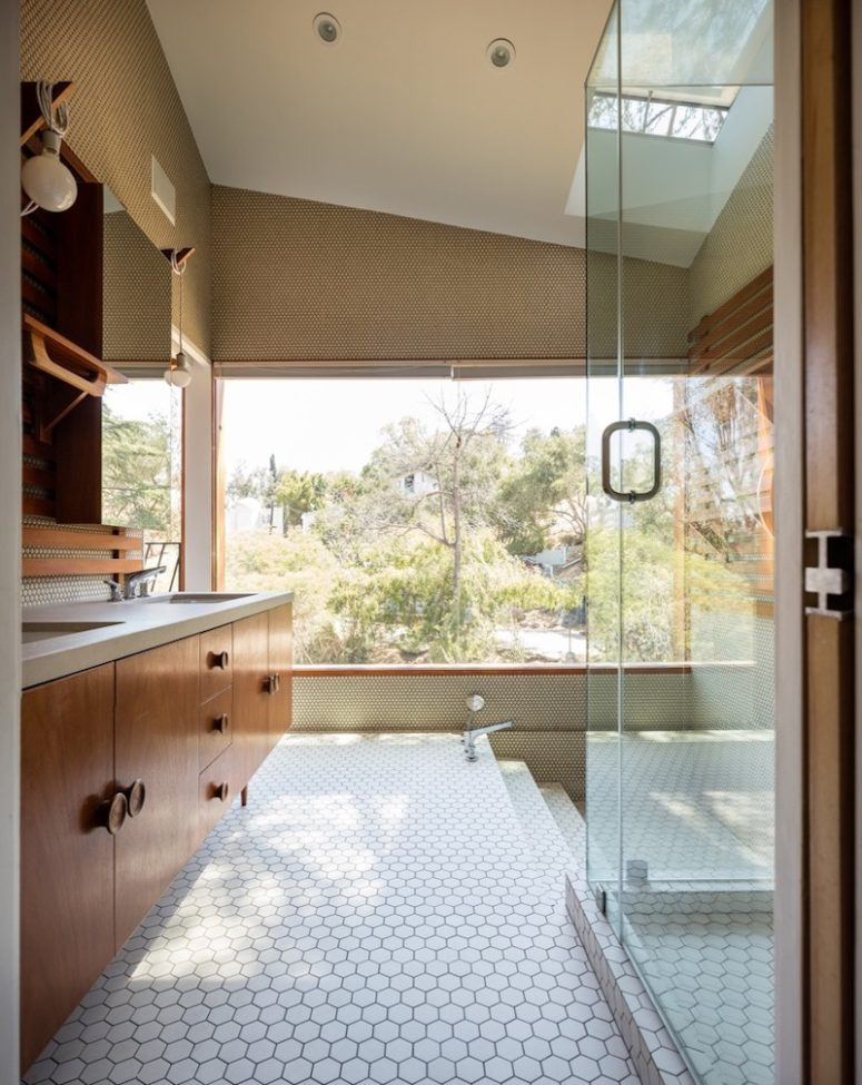 The bathroom is clad with hex tiles and there's a creative bath area with a view