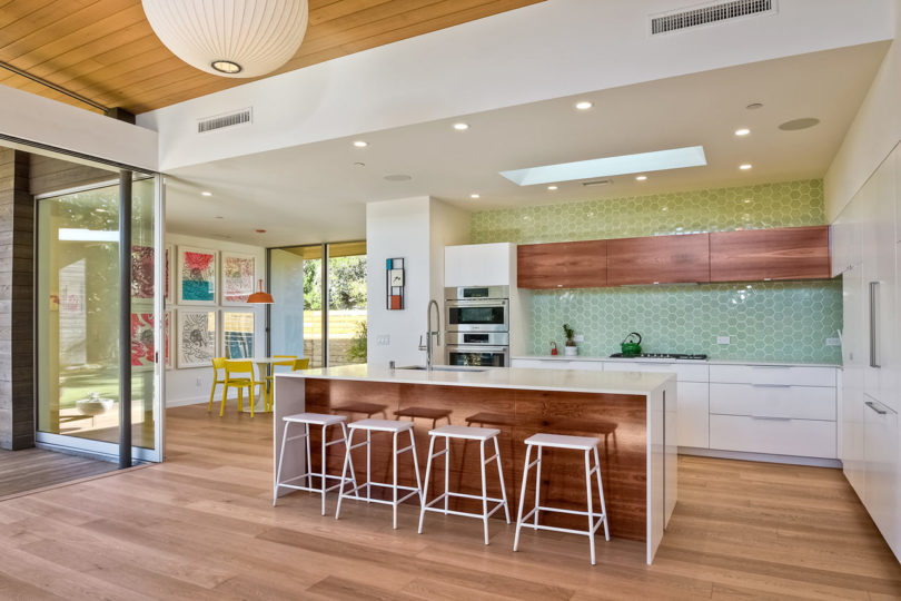 The kitchen is white and with stained wood touches for a cozy feel, I love the green hex tiles that ocver one of the walls