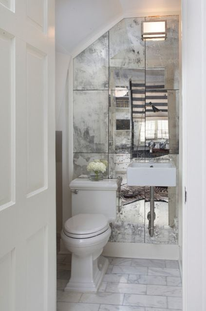 a faded mirror wall can make a tiny powder room look bigger and more stylish at the same time