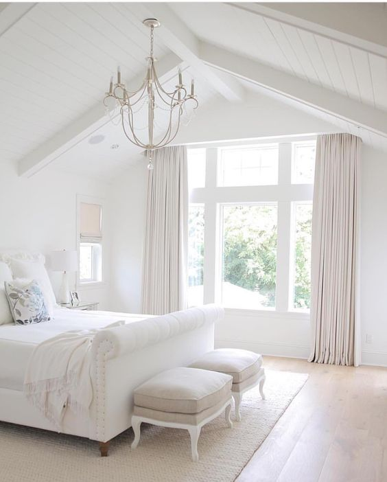 a white upholstered bed, curtains and a cozy rug add texture and comfiness to the bedroom