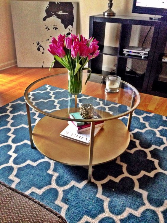 an elegant round copper and light wood and glass table with two tabletops for storage for a girlish space