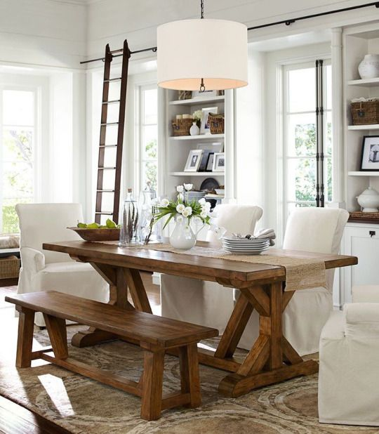 in this white space the trestle dining table is highlighted with a matching bench