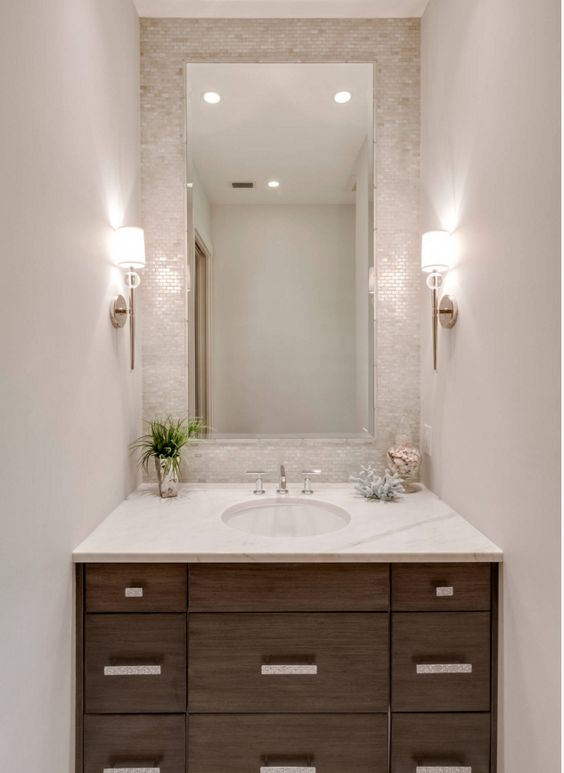 small mother of pearl tiles accentuate the sink zone and spruce up a neutral bathroom