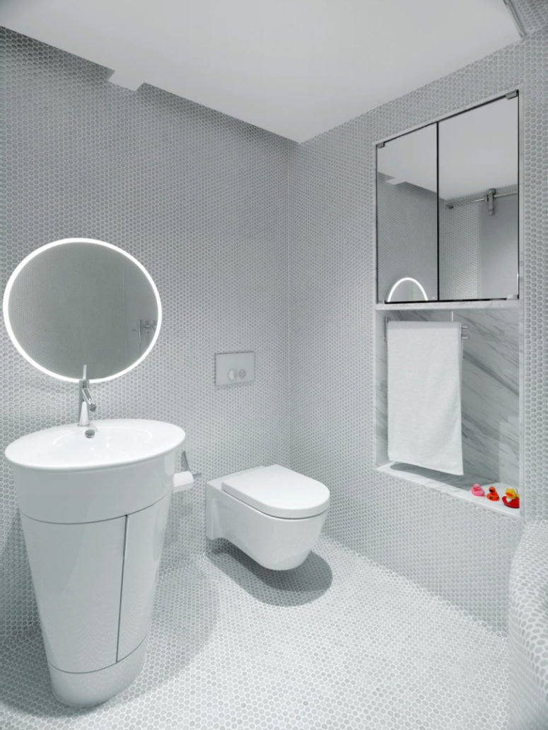 The second bathroom is clad with hex penny tiles and with modern appliances