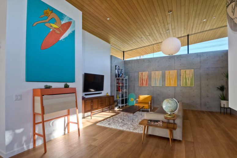 The walls are done of concrete, and the floors and ceilings are wooden, so bright artworks stand out in such spaces