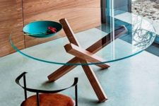 11 a clear round glass top and wooden legs that remind of usual firewood looks cool and eye-catchy