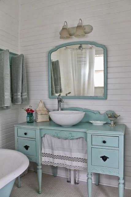 a mint-colored desk turned into a vanity with a curtain and a matching mirror