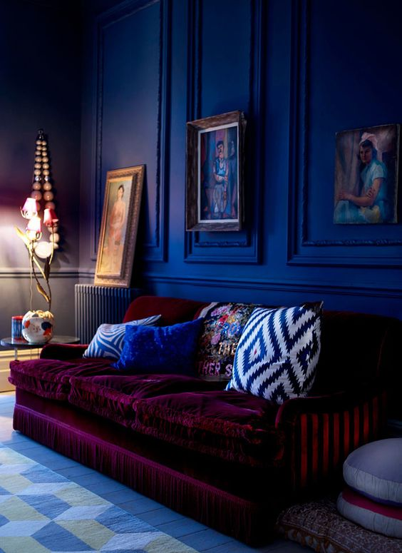 a moody cobalt blue space is made outstanding with a plum-colored velvet sofa