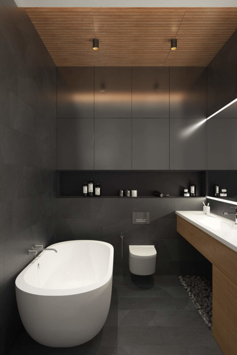 The master bathroom is done in matte charcoal grey, with pebbles for a spa feel and a free-standing bathtub