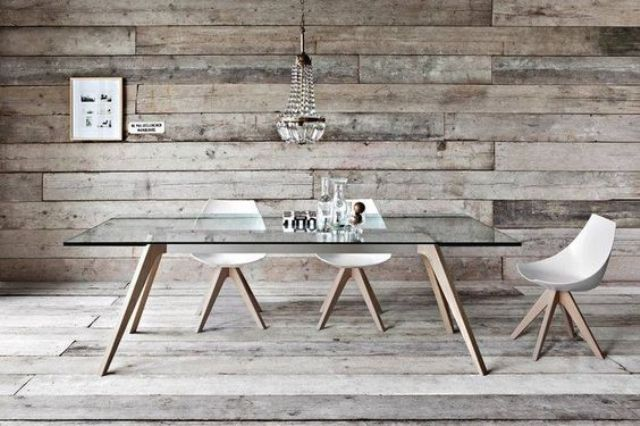 a dining table with wooden legs and a glass tabletop for a rustic space with a modern feel