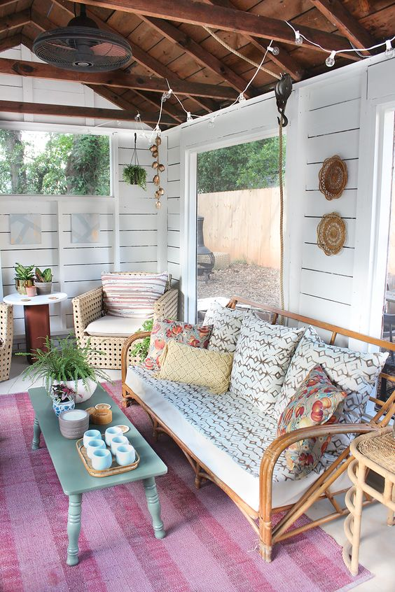 a rustic and vintage living room with panoramic windows, rattan furniture and boho decorations