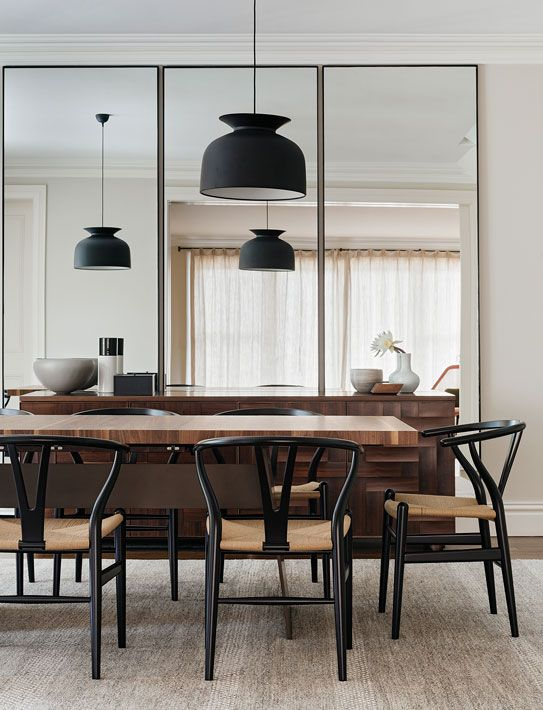 a trio of three tall mirrors makes the dining room look bigger