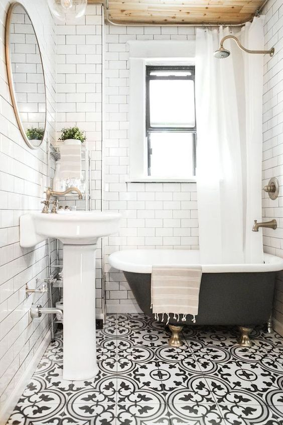 a white vintage-inspired bathroom with patterned black and white floor tiles