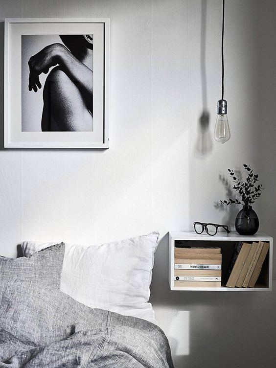 an open white box floating nightstand has a storage space inside and a top to place something