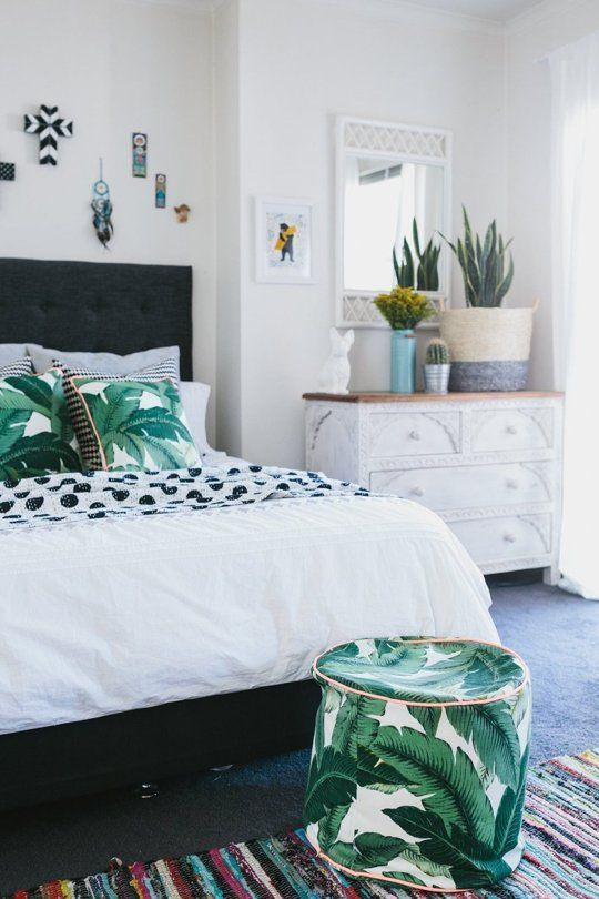 tropical leaf print pillows and a matching ottoman for a summer bedroom