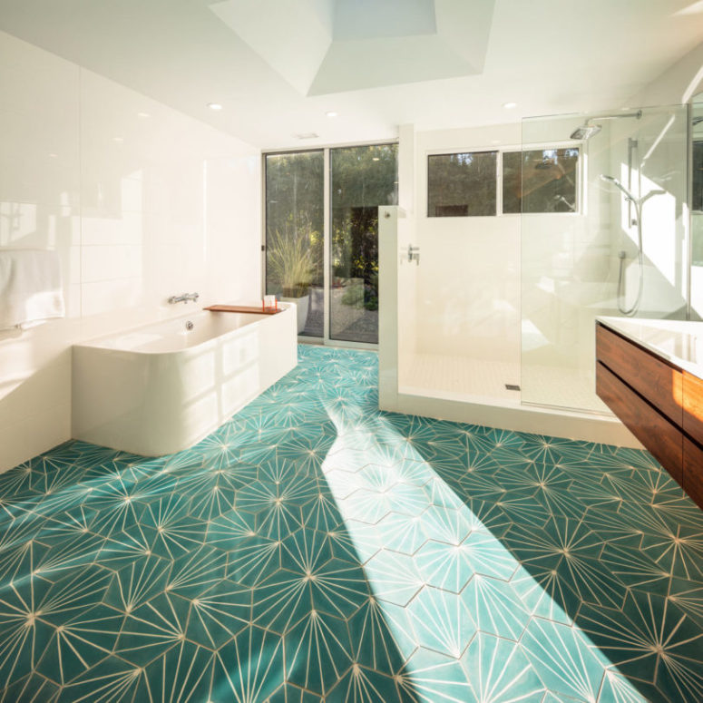 The bathroom boasts of green geo tiles and a gorgeous view, plus it can be opened to outdoors