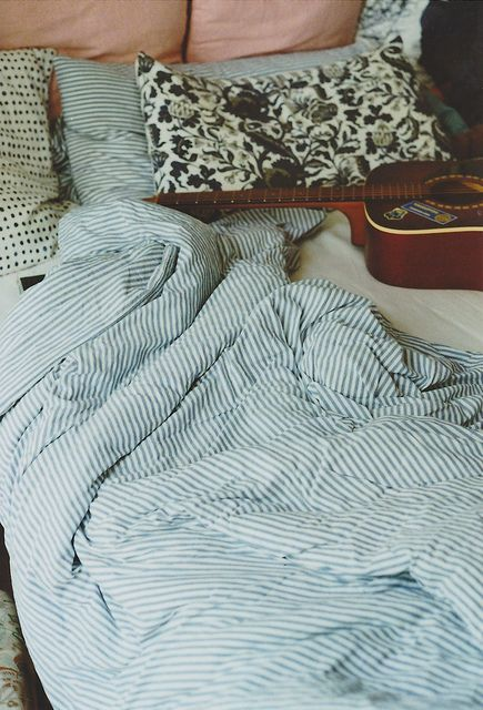 a blue striped bedding set and some accent botanical print pillows