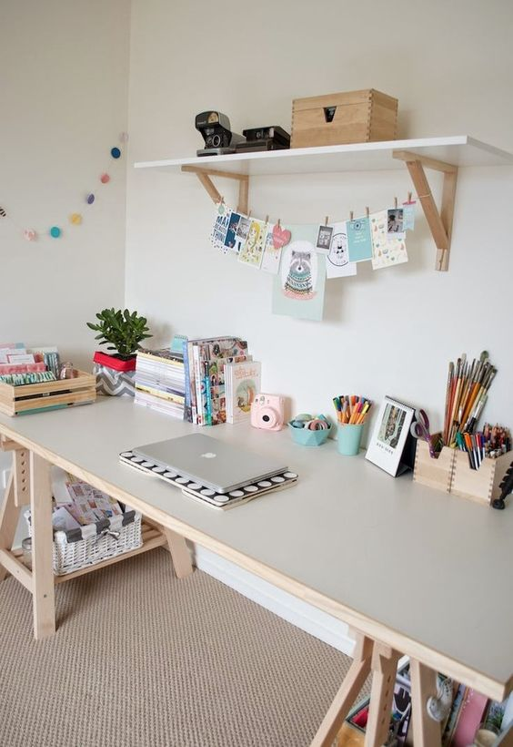 a kid's study space with a light-colored trestle desk, which has storage compartments