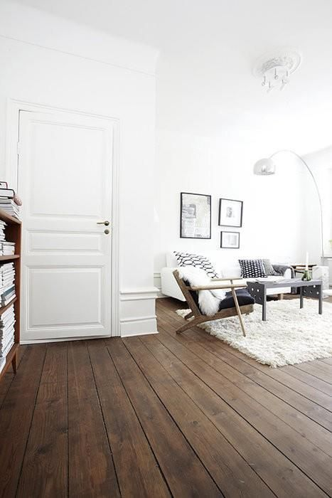 a white Scandinavian living room is made cool with dark stained wooden floors
