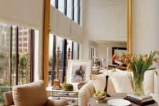 13 an oversized wooden frame mirror highlights the double height ceiling and makes the living room bigger