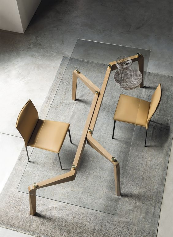 a modern and industrial table on sculptural wooden legs, metallic touches and a glass tabletop, matching beige leather chairs