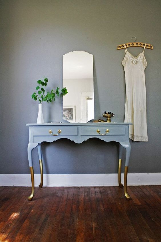 a vintage desk painted blue, with gilded legs and brass handles to use as a vanity