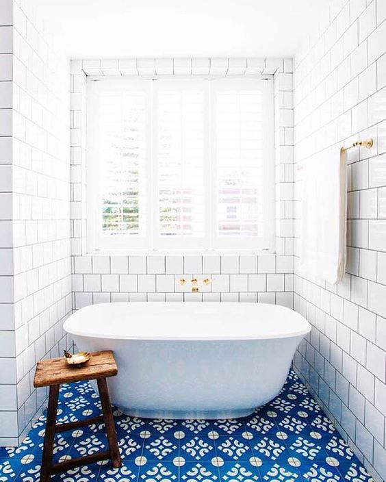 blue patterned tiles on the floor and white subway tiles for a gorgeous bathroom