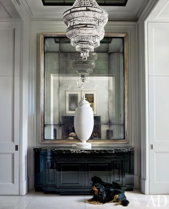 oversized mirror in a metallic frame with a large vintage chandelier look exquisite and adorable