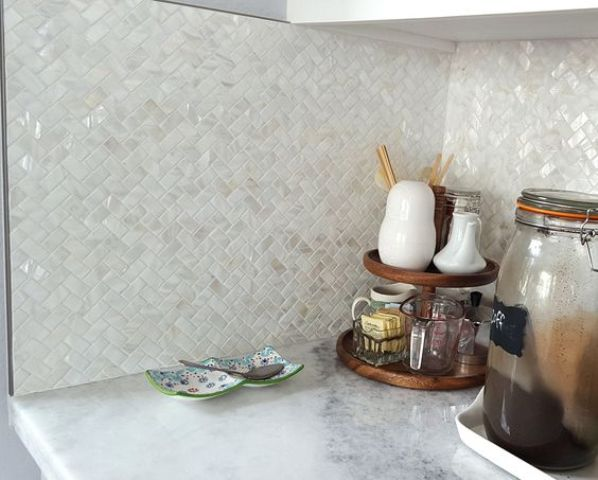 mother of pearl tiles clad in a herringbone pattern for sprucing up a neutral kitchen