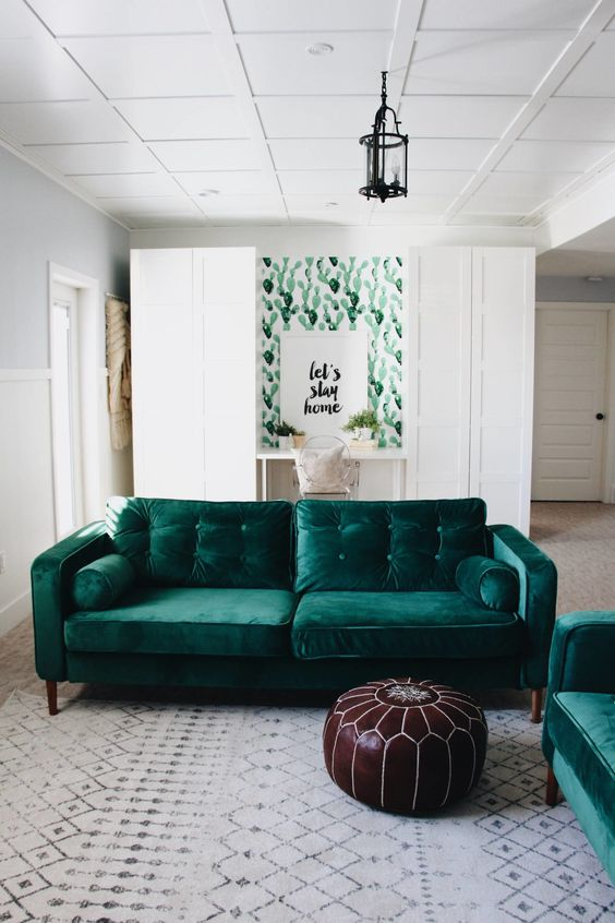 two emerald velvet sofas echo a cactus print wall