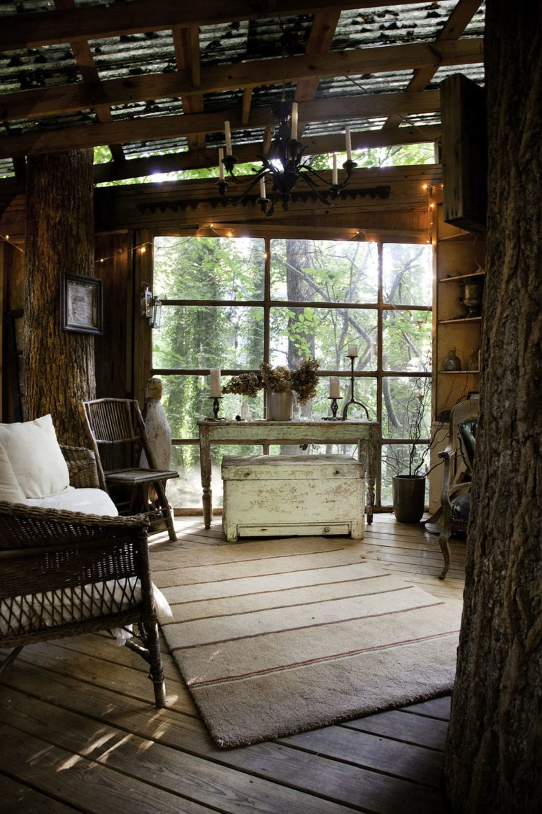 a treehouse she shed decorated as a shabby chic living room with wicker furniture