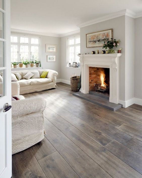 a white living room with grey and brown stained wooden floors, textural upholstery also adds to the space