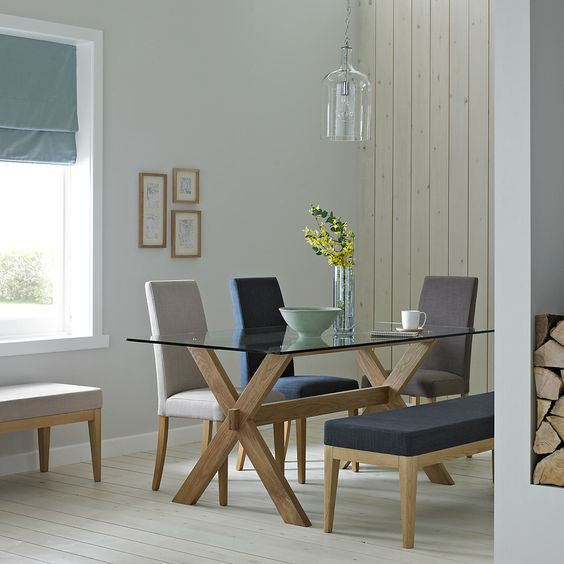 a trestle table with a glass tabletop and comfy upholstered chairs for a cozy and simple dining space