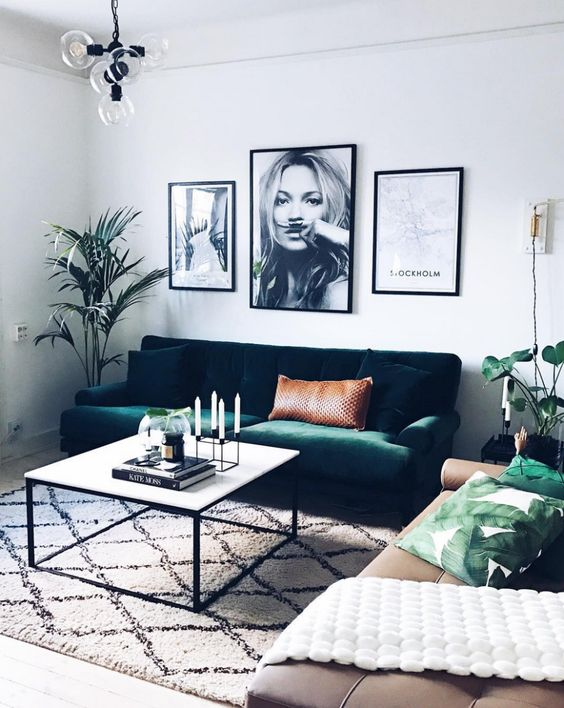an emerald green velvet sofa echoes with greenery and leaf print pillows and makes this space lively