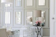 17 repeated mirrors in large white frames on the wall make the shabby chic space a bit more modern
