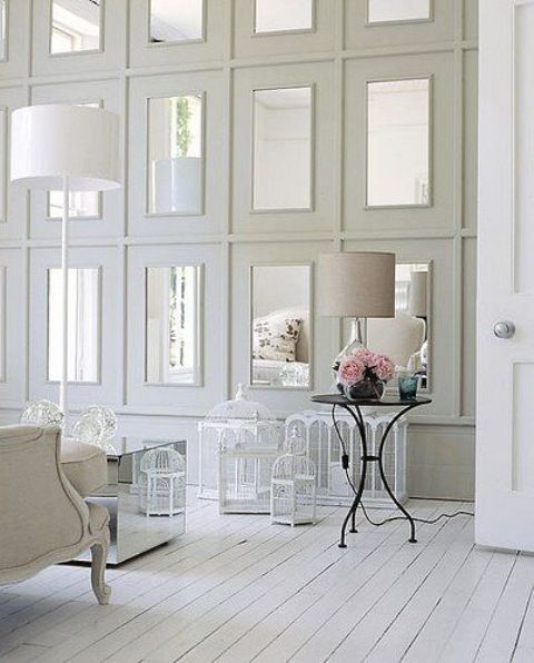 repeated mirrors in large white frames on the wall make the shabby chic space a bit more modern
