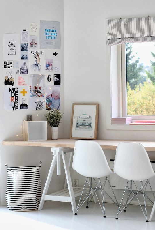 a Scandinavian workspace for two with a long trestle desk on white legs, which is used instead of a windowsill