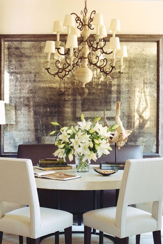a dining room made more refined and adorable with an oversized faded mirror in a vintage frame