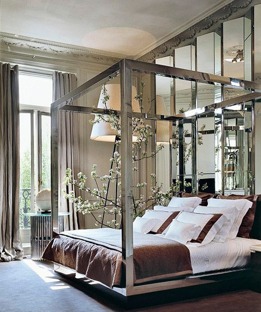 a geo mirror wall and a mirror bed frame add interest to the bedroom