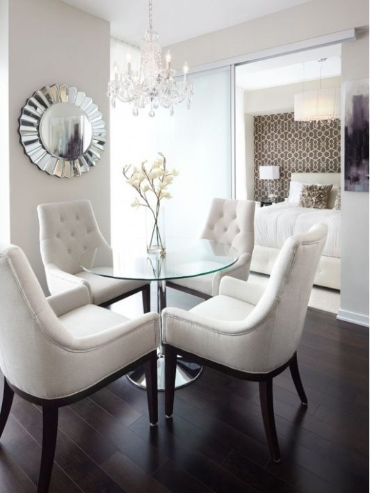 glam timeless dining area with dark wooden floors and matching chairs with white upholstery