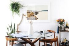18 mid-century modern inspired dining table with a sculptural wooden base and a round glass tabletop, matching chairs with leather upholstery