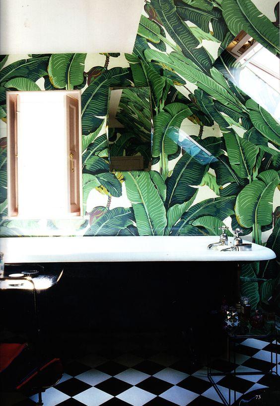 retro-inspired bathroom with palm leaf print wallpaper and a black bathtub