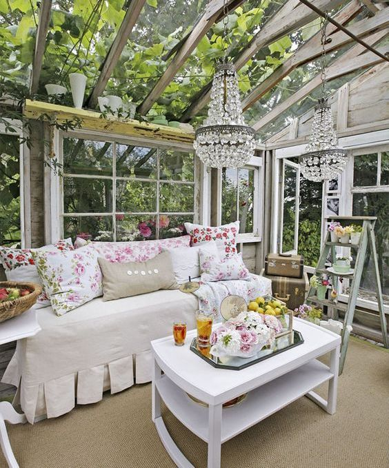 vintage-inspired glam she shed, a daybed with floral print pillows and glam chandeliers