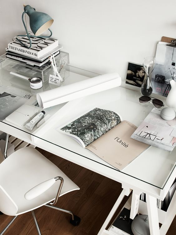 a Scandinavian home office with a white desk and a glass top over it to use the space inside for storage