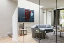 19 a geometric mirror wall visually doubles the living room and it looks much bigger