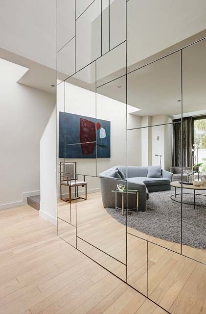 a geometric mirror wall visually doubles the living room and it looks much bigger