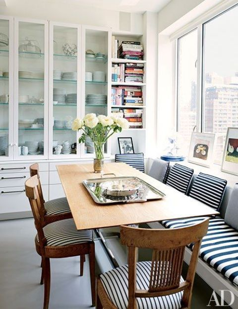 striped upholstery of the bench and chairs adds style to this dining space by the window