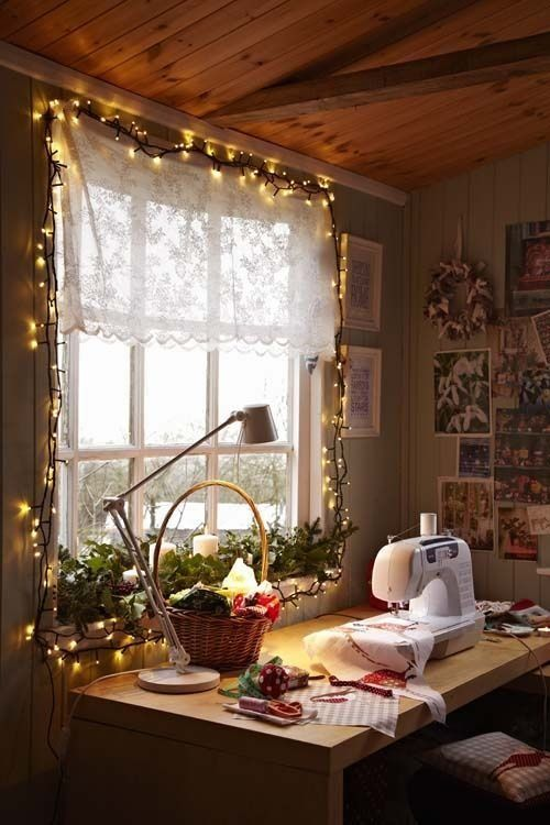 a cozy sewing room with string lights, a table and an inspiration wall with photos