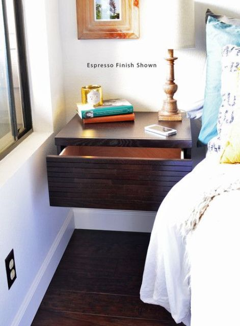 a dark stained floating nightstand with a large drawer