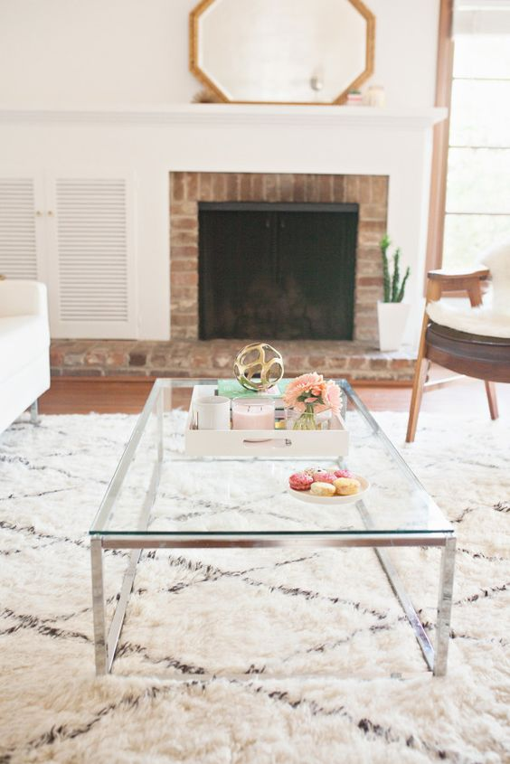 a low coffee table on nickel legs with a glass tabletop can fit a modern or even a boho space
